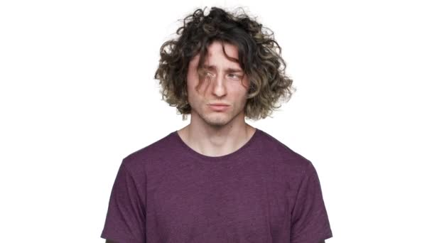 Portrait of positive hairy man in casual t-shirt grinning and blowing locks of his curly hair, isolated over white background slow motion. Concept of emotions