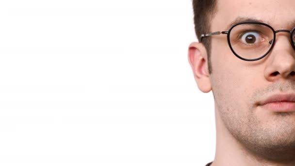 Polovina strany portrét kavkazské vážný muž 20s nošení brýlí vypoulené oči a údivu, izolované nad bílým pozadím. Pojetí emocí