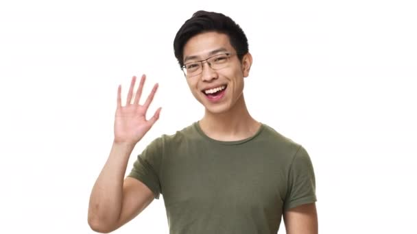 0824191d673a Portrait of happy asian man wearing eyeglasses and basic t-shirt greeting  with waving hand on camera, isolated over white background.