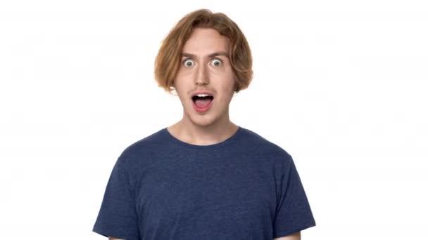 Portrét překvapeného muže v ležérní tričko, směje se dokonalé zuby a vyvalenýma očima v úžasu, izolované na bílém pozadí. Pojetí emocí