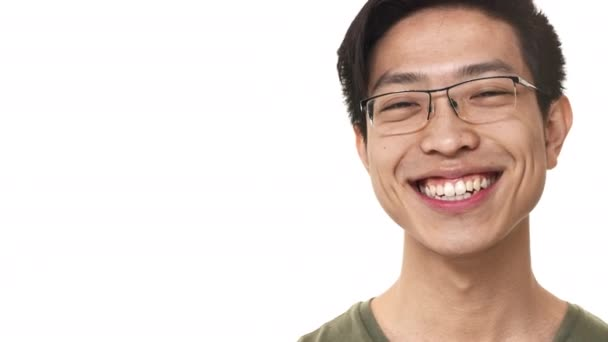 Portrait closeup of content chinese man 20s wearing eyeglasses smiling with perfect teeth near copy space, isolated over white background. Concept of emotions