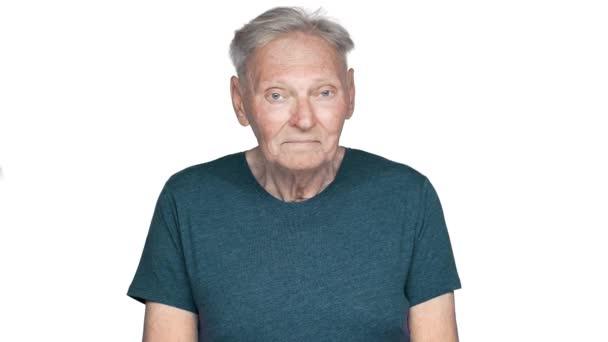 Portrét druhu a veselý stařík ve věku 80 let s šedými vlasy v základní tričko při pohledu na fotoaparát s úsměv v pomalém pohybu, izolované na bílém pozadí