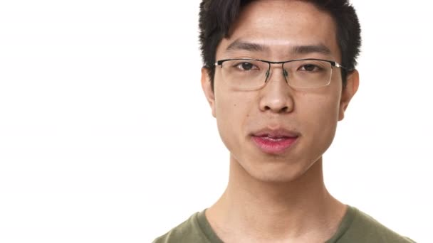 Portrait closeup of handsome asian man 20s wearing eyeglasses and basic t-shirt smiling and winking, isolated over white background. Concept of emotions