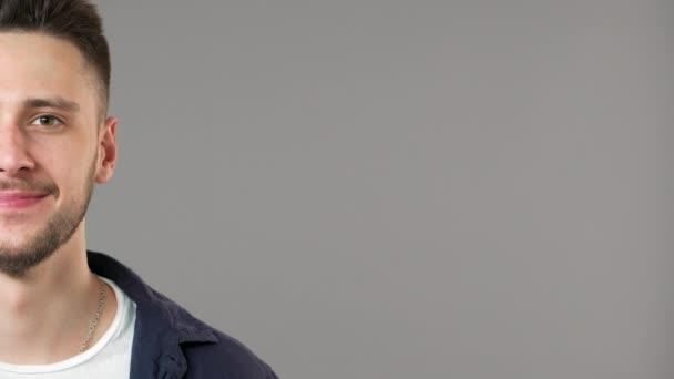 Polovina straně portrét atraktivní vousatý muž nosí ležérní oblečení se usmívá na kameru v blízkosti místa kopie, izolované nad šedým pozadím v detailním studio. Pojetí emocí