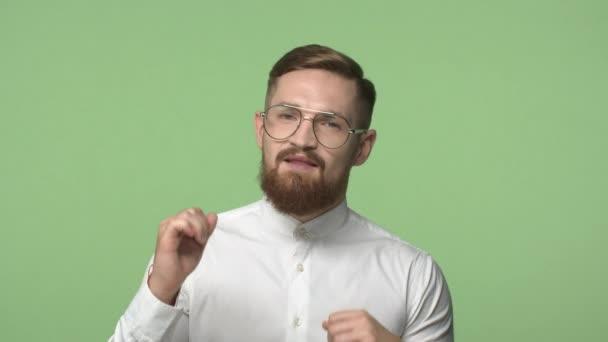 Úspěch, strana a volný čas koncept. Slowmo šťastný, bezstarostný pohledný vousatý chlap v brýlích a košili, mužské tělo, zvedající ruce, tanec, těší víkendy, dnes žádná práce, zelené pozadí