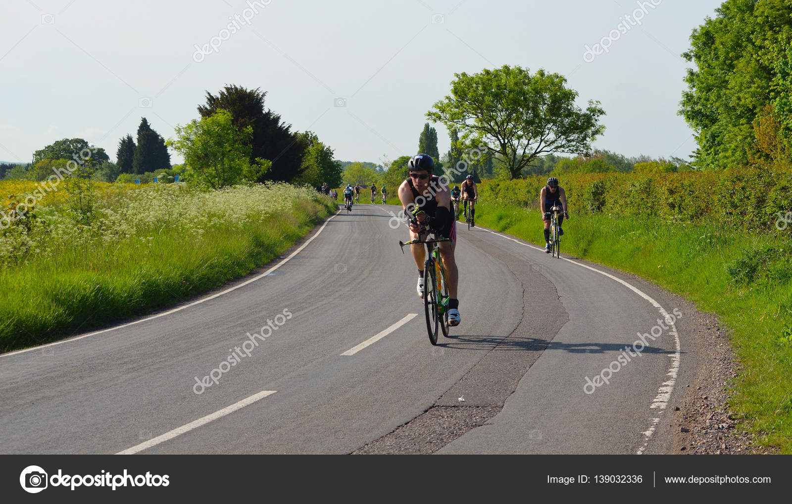 Triathletes on road cycling stage of triathlon fields and