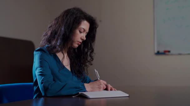 curly brunette woman making notes in school classroom