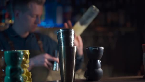 Barista bereitet exotischen Cocktail mit Zitronenlikör und Saft zu