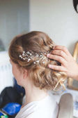 Hairdresser makes wedding hairstyle bride with blond hair