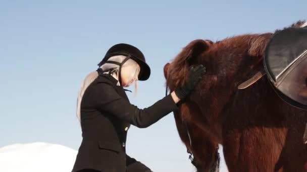 Krásná mladá dívka žokej, péče o koně v zimě