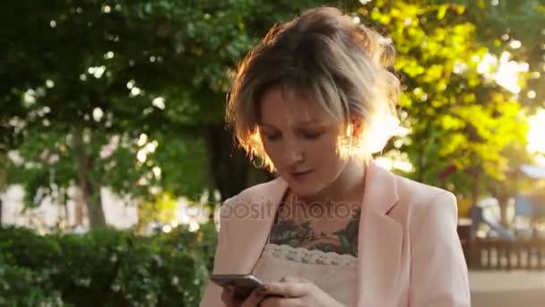 Atraktivní mladá žena, procházky v parku a používá smartphone