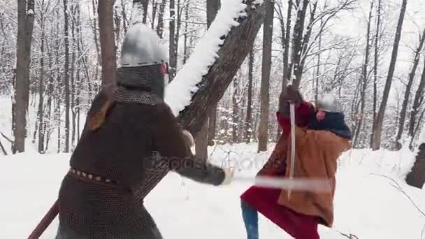Medieval frankish and viking warriors in armor fighting in a winter forest with swords and shields