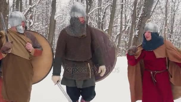Medieval frankish, irish, viking warriors in armor walking in a winter forest with swords shields