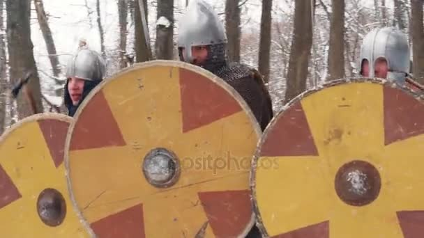 Medieval frankish, irish, viking warriors in armor fighting in a winter forest with swords shields