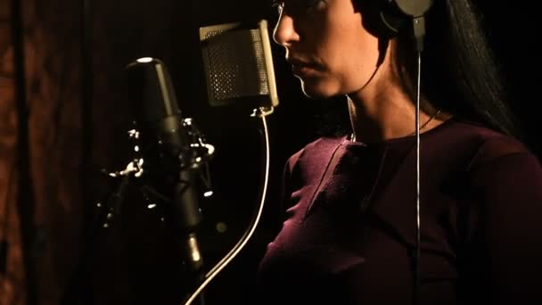 Portrét mladé ženy nahrávající píseň v profesionálním studiu
