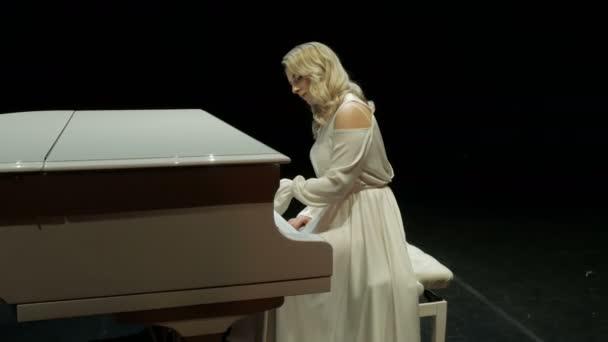 Profi zongorista fehér ruhában játszik egy nagy zongorán a színpadon a koncertteremben tompa fénnyel.