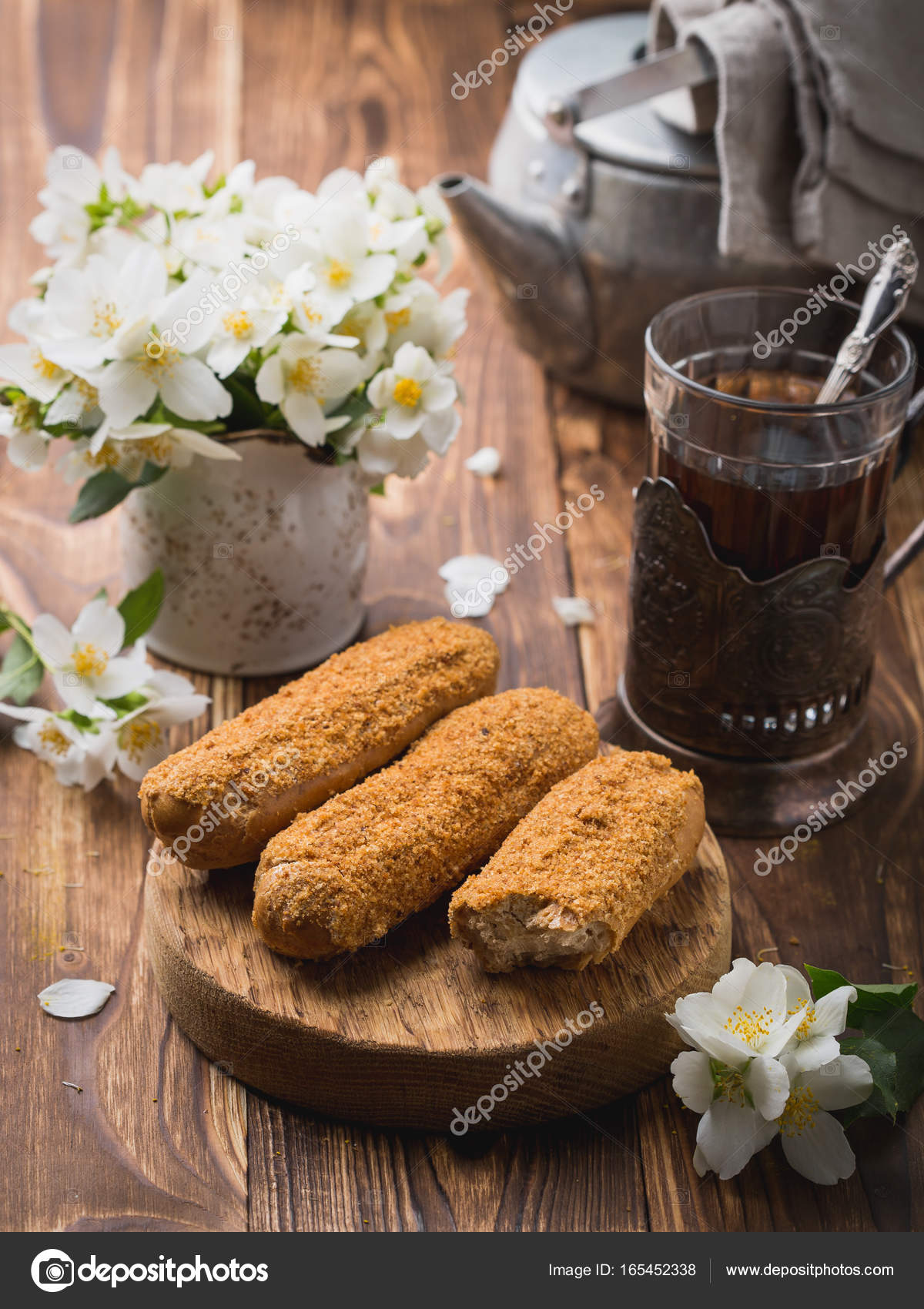 Eclairs mit Tee in ein Becherglas. Holztisch Blumen auf dem Tisch ...