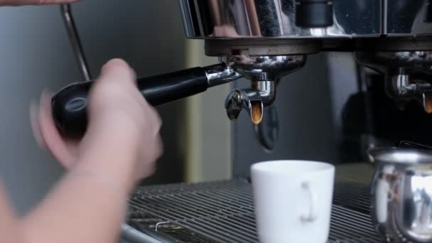 Full process of making coffee on professional coffee machine. Barista preparing double espresso, pouring it in cup.