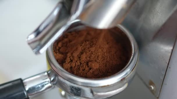 Barista mele kávu do držáku na mlýnku na kávu, pro výrobu americano, cappuccino, latte.