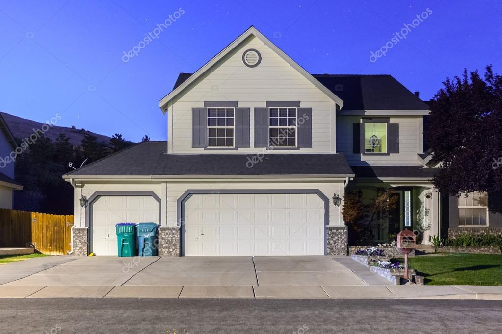Big Luxury House With Triple Garage Doors At Dusk Night In Suburbs