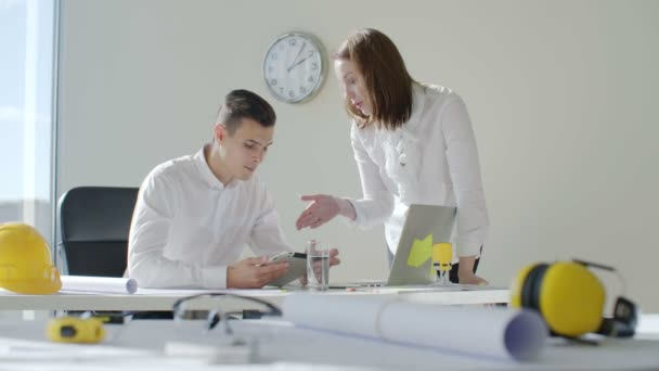 Architector a jeho asistent sedí u stolu v bílé moderní kancelář stavební společnosti, pracují na projektu výstavby budovy