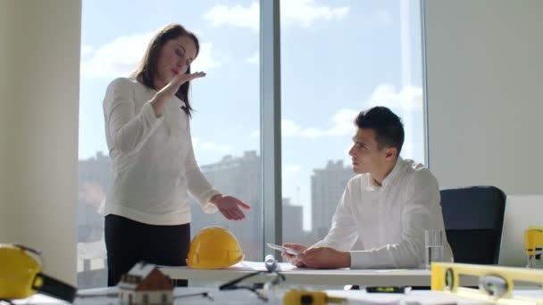 Architekti sedí u stolu v bílé moderní kanceláře stavební firmy před velké panoramatické okno. pozadí panoramatu města. Pracují na projektu výstavby budovy