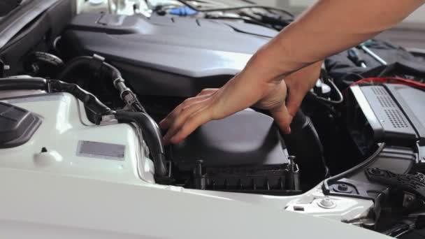 Auto mechanik měnící vzduchový filtr v automobilu. Auto servis v dílně