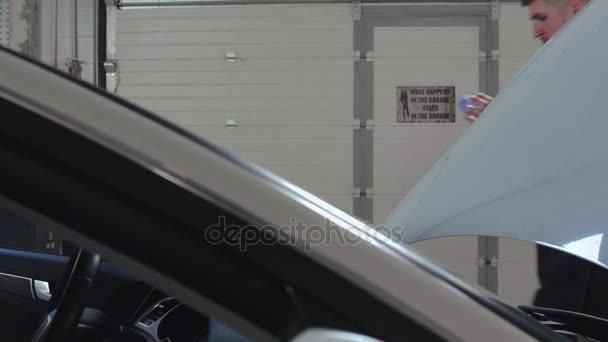 Automechanik, otřel si rukou po opravě automobilu. Auto diagnostika počítače