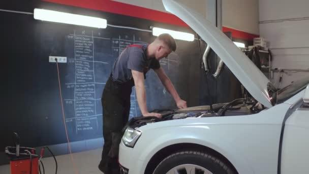 Auto mechanik otevírání olejové nádrže vozu a kontroly auto motor. Auto servis