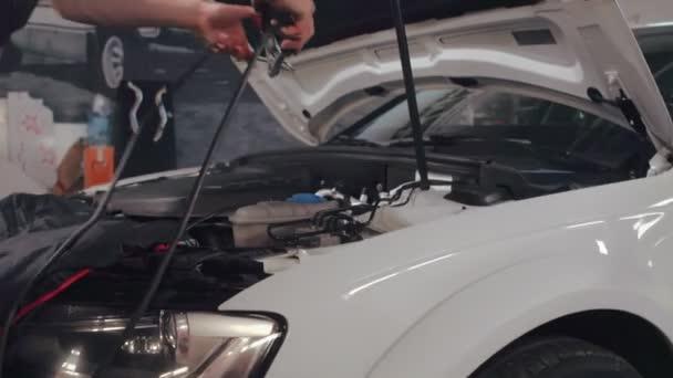 Měření napětí na autobaterii v servisu auto mechanik muž. Servis automobilů