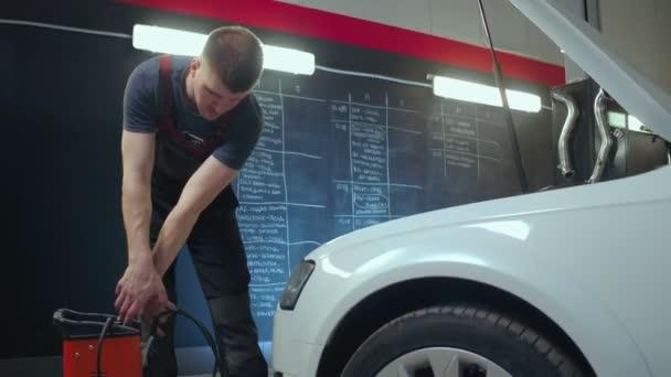 Auto služby pracovník kontroly napětí na autobaterii. Auto čerpací stanice