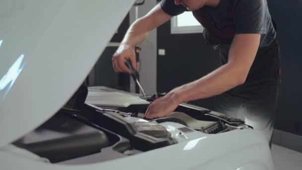Opravit člověka pomocí opravy, fotografované nástroje pod kapotou vozu v auto servis