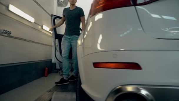 Spokojený zákazník vstupující z auta a ukazuje palec. Servis automobilů