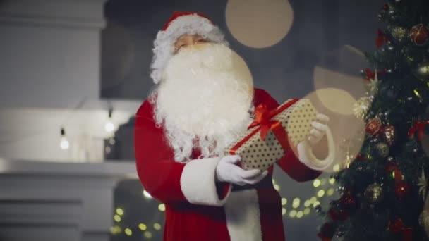 Santa Claus drží v ruce vánoční krabičce na pozadí novoroční strom
