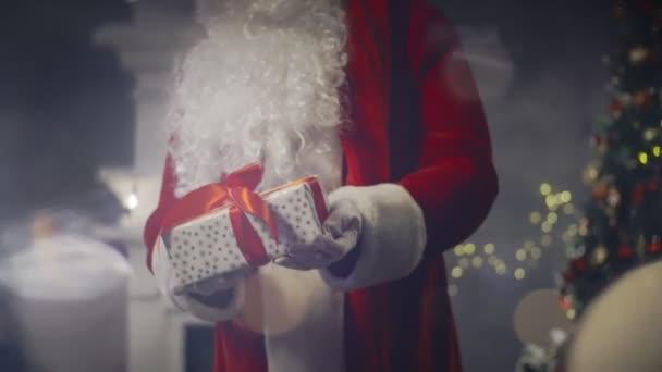 Santa Claus drží v rukou přítomné na nový rok na pozadí vánoční stromeček