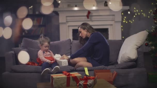 Mother together daughter open holiday present on background Christmas tree