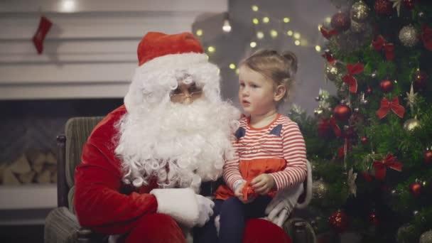 Santa Claus drží malou holčičku na kolena na pozadí novoroční strom v domácnosti