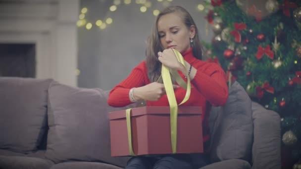 Mladá žena balení dovolená krabičce a olepování páskou k Vánocům