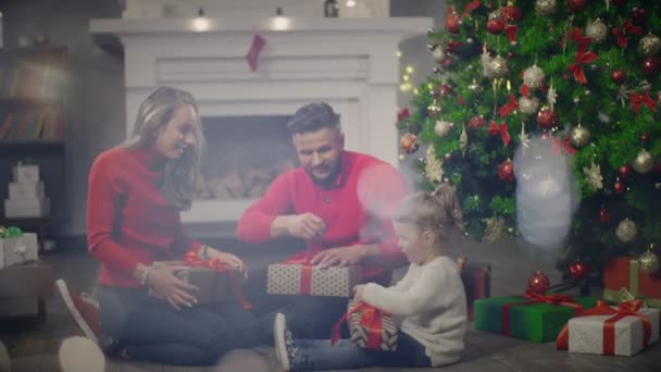 Šťastná rodina rozbalování dárků box sedí na podlaze na pozadí novoroční strom