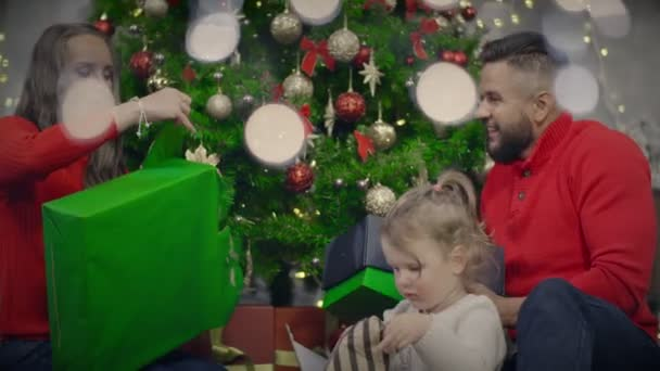 Young family opening presents box sitting on floor on background Christmas tree