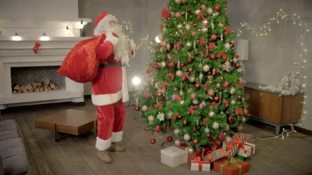 Vidám Mikulás tánc a jelenlegi táska mögött vissza közel karácsonyfa
