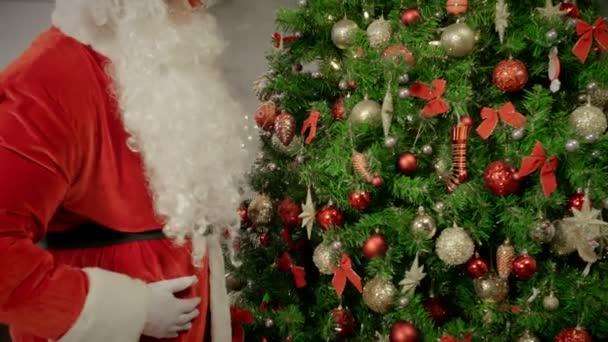 Santa Claus, megható, és keresi a gyönyörű karácsonyfa díszítés