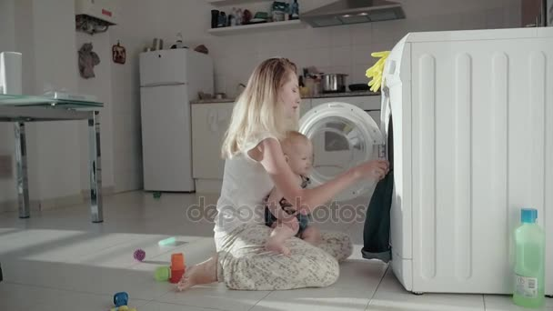 Young mother sitting on floor front washing machine and holding baby in arms