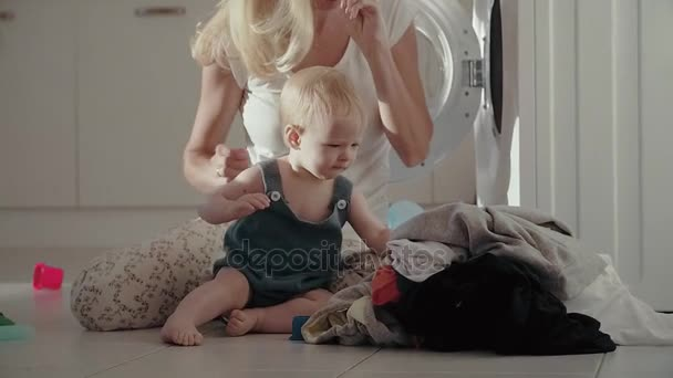 Young mother and baby playing with toys opposite washing machine