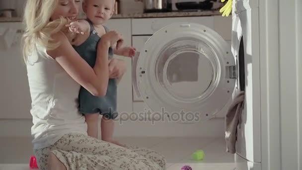 Junge Mutter Baby Hände festhalten und mit Waschmaschine