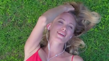 Young woman lying on green grass on summer day and listening music on headphones