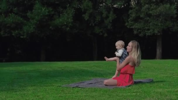 Happy mom and baby playing on green grass at meadow in aprk at sunny day