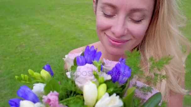 Happy woman in red dress sniffing bouquet flowers
