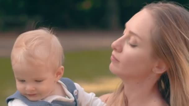 Portrait young mom and baby on background summer nature. Mom and baby closeup