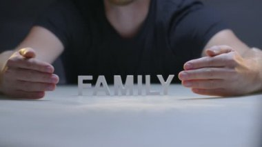 Man hands showing word family composed from white letters on gray background
